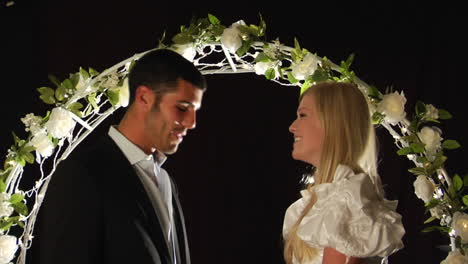 Bride-and-groom-laughing-under-a-flower-arch
