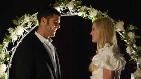 Bride-and-groom-stand-under-an-arch-of-flowers-as-the-man-slips-a-ring-on-the-woman-s-finger