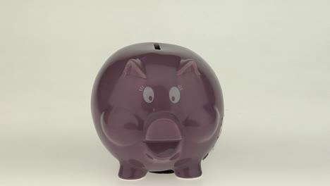 Die-Hand-Einer-Frau-Wirft-Eine-Münze-In-Ein-Rosa-Sparschwein