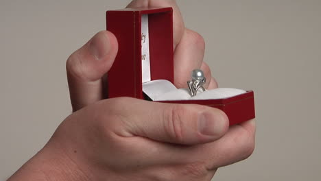 A-man-s-hands-open-a-red-jewelry-box-that-reveals-a-pearl-ring