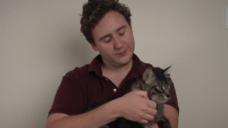 A-man-holds-and-pets-a-striped-cat