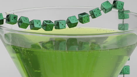 Beads-of-green-dice-adorn-a-cocktail-glass