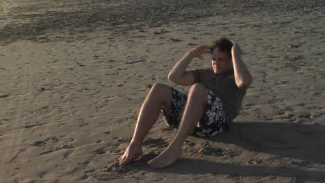 A-man-does-situps-on-a-sandy-beach