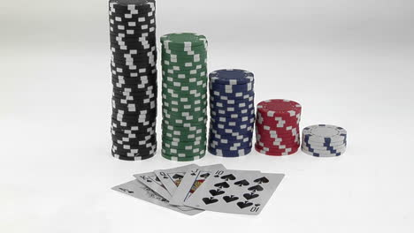 Stacks-of-poker-chips-sit-in-a-row-arranged-by-value-behind-a-deck-of-playing-cards