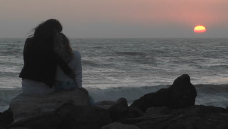 A-mother-and-her-young-daughter-sit-on-a-rock-facing-the-sea-at-golden-hour