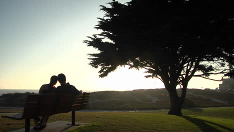 A-couple-snuggles-on-a-park-bench