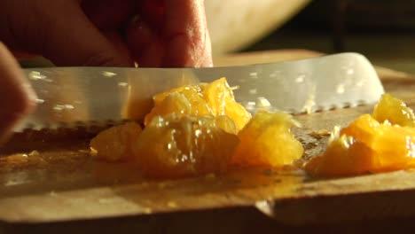 A-woman-slices-an-orange-on-a-cutting-board