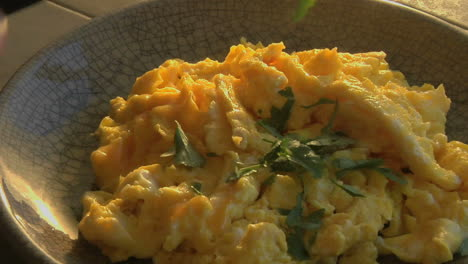 A-slow-pull-into-a-bowl-of-scrambled-eggs-as-parsley-is-chopped