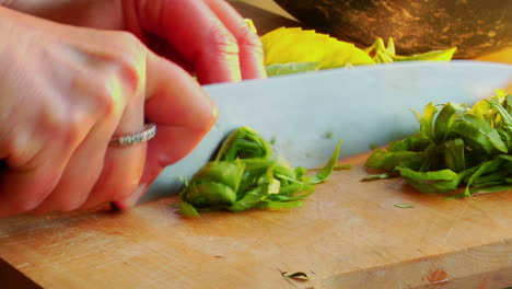 A-woman-chef-preps-a-salad-by-chopping-basil-on-a-wooden-cutting-board