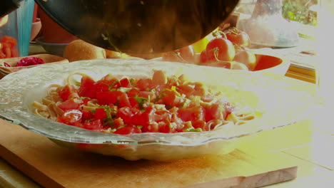 A-woman-chef-prepares-a-meal-by-pouring-fresh-cooked-sauce-onto-a-steaming-bowl-of-pasta