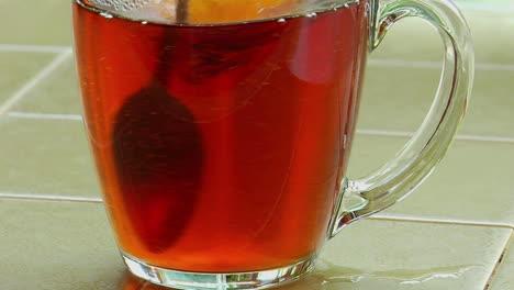 Zucker-In-Eine-Klare-Glastasse-Tee-Gegossen-Und-Mit-Einem-Löffel-Verrührt
