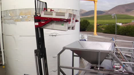 A-forklift-delivers-crushed-grapes-to-a-bladder-press-for-added-juice-extraction