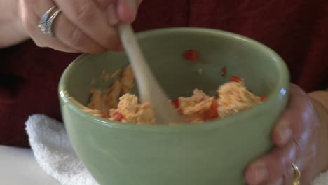 A-woman-stirs-a-tomato-and-cream-cheese-dip