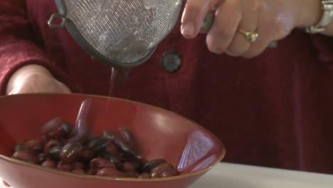 A-woman-pours-olives-from-a-strainer-into-a-bowl