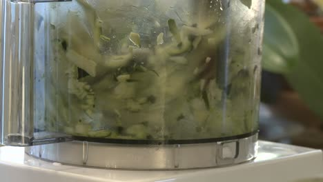 Close-up-of-zucchini-being-chopped-in-a-food-processor