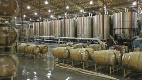 A-cellar-crew-tops-off-wine-barrels