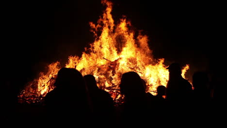 People-stand-in-front-of-a-large-raging-bonfire-at-night
