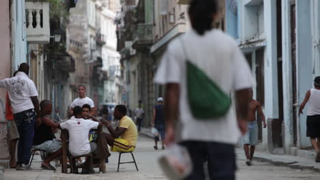 People-walk-and-play-dominos-on-the-cobblestone-strets-of-Havana-Cuba