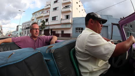 A-man-rides-in-a-convertible-classic-car-in-Havana-Cuba