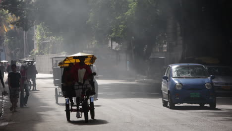 A-car-and-pedicab-drive-down-a-smoky-road-in-Havana-Cuba
