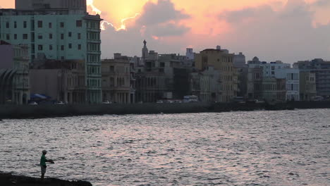 A-fisherman-stands-before-the-skyline-of-Havana-Cuba-at-sunset