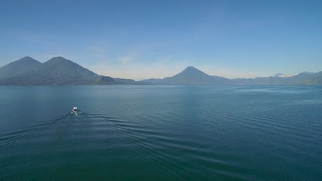 Aerial-over-a-boat-on-Lake-Amatitlan-in-Guatemala-reveals-the-Pacaya-Volcano-in-the-distance-1