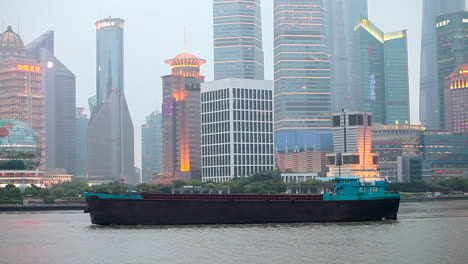 The-dusk-skyline-of-Shanghai-China-with-river-traffic-foreground-and-boats-passing