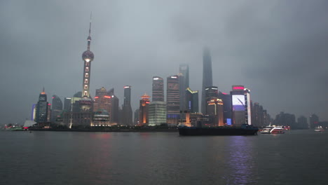 The-night-skyline-of-Shanghai-China-with-river-traffic-foreground