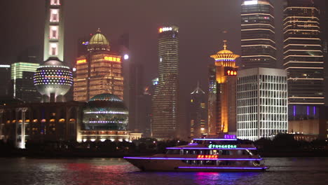 The-vivid-night-skyline-of-Shanghai-China-with-river-traffic-foreground