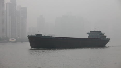 A-barge-travels-on-the-Pearl-River-in-Shanghai-China-in-smog-and-fog