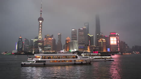 The-vivid-night-skyline-of-Shanghai-China-with-river-traffic-foreground-1