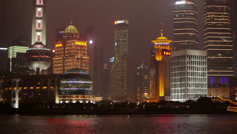 The-vivid-night-skyline-of-Shanghai-China-with-river-traffic-foreground-and-illuminated-tall-ship-passing