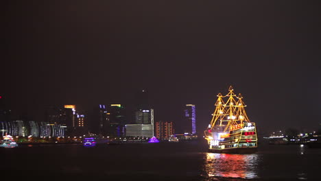 The-night-skyline-of-Shanghai-China-with-river-traffic-foreground-and-illuminated-tall-ship-passing