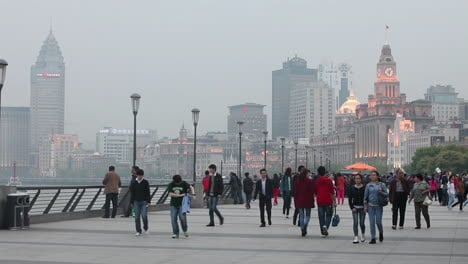 People-walk-on-a-broad-promenade-on-the-waterfront-of-Shanghai-China