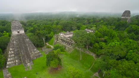 Great-aerial-shot-over-the-Tikal-pyramids-in-Guatemala-2