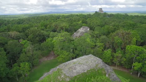 Spectacular-aerial-shot-over-the-treetops-and-Tikal-pyramids-in-Guatemala-1