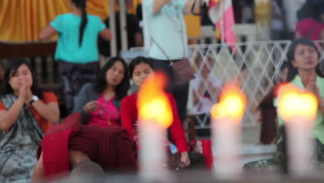 Burmese-people-pray-at-a-Buddhist-temple-with-candles-foreground