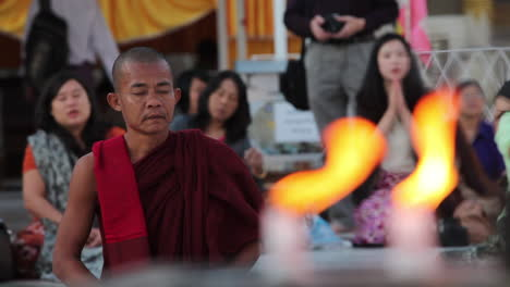 A-Burmese-monk-prays-at-a-Buddhist-temple-with-candles-foreground