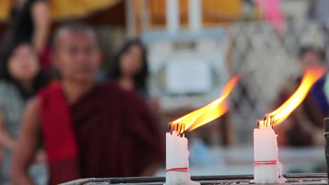 A-Burmese-monk-prays-at-a-Buddhist-temple-with-candles-foreground-1