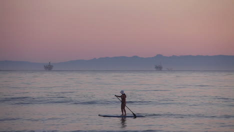 A-paddle-boarder-rows-across-the-ocean-at-sunset