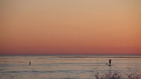 A-paddle-boarder-rows-across-the-ocean-at-sunset-1
