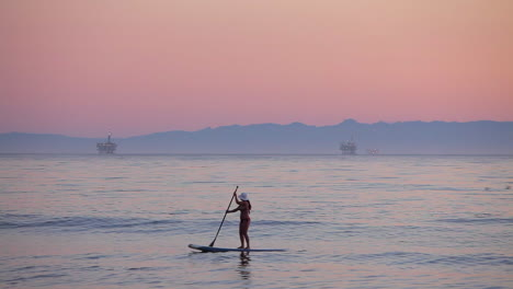 A-paddle-boarder-rows-across-the-ocean-at-sunset-2