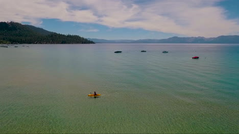 An-aerial-over-a-woman-paddling-a-kayak-across-Lake-Tahoe-1