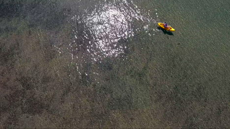 A-high-aerial-over-a-woman-paddling-a-kayak-across-Lake-Tahoe