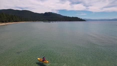 A-woman-in-a-yellow-kayak-paddles-on-the-sunlight-crystal-clear-water-of-Lake-Tahoe-on-a-bright-summer-day