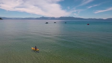 A-woman-in-a-yellow-kayak-paddles-on-the-sunlight-crystal-clear-water-of-Lake-Tahoe-on-a-bright-summer-day-1