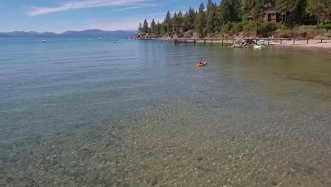 A-woman-in-a-yellow-kayak-paddles-on-the-sunlight-crystal-clear-water-of-Lake-Tahoe-on-a-bright-summer-day-4