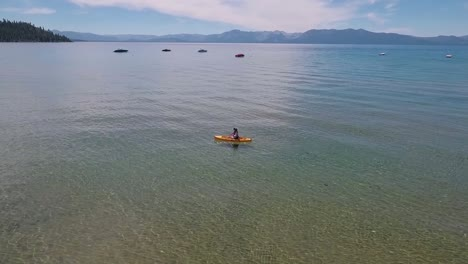 A-woman-in-a-yellow-kayak-paddles-on-the-sunlight-crystal-clear-water-of-Lake-Tahoe-on-a-bright-summer-day-5