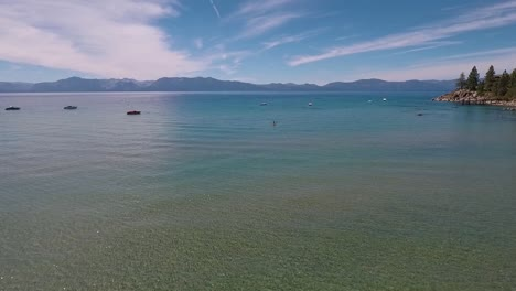 A-woman-in-a-yellow-kayak-paddles-on-the-sunlight-crystal-clear-water-of-Lake-Tahoe-on-a-bright-summer-day-6