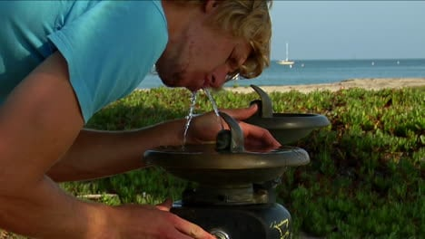 A-man-sips-water-at-a-drink-fountain